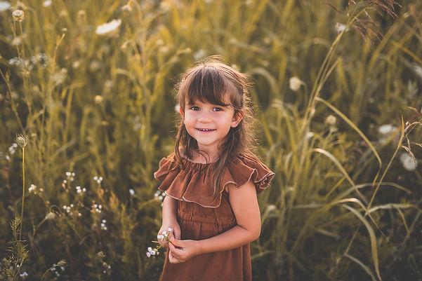 bambina in un campo di fiori