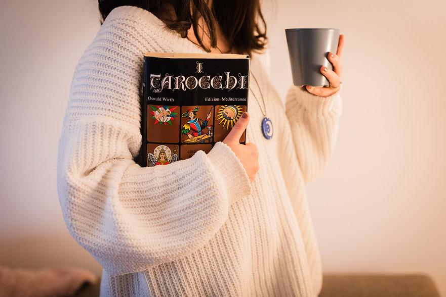 ragazza con maglione bianco che tiene in mano un libro di tarocchi e una tazza di tisana