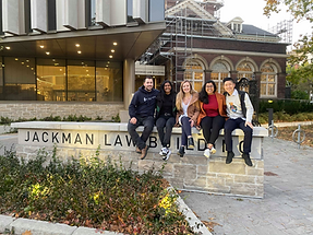 PBSC U of T students sitting on the Jackman Law sign