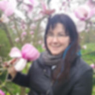 Caelin the petsitter standing under pink maragold tree