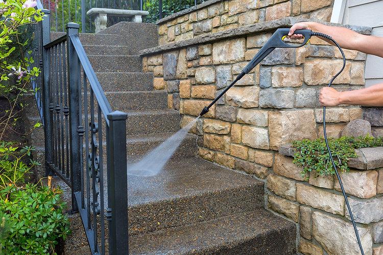 handyman pressure washing stairs at home.