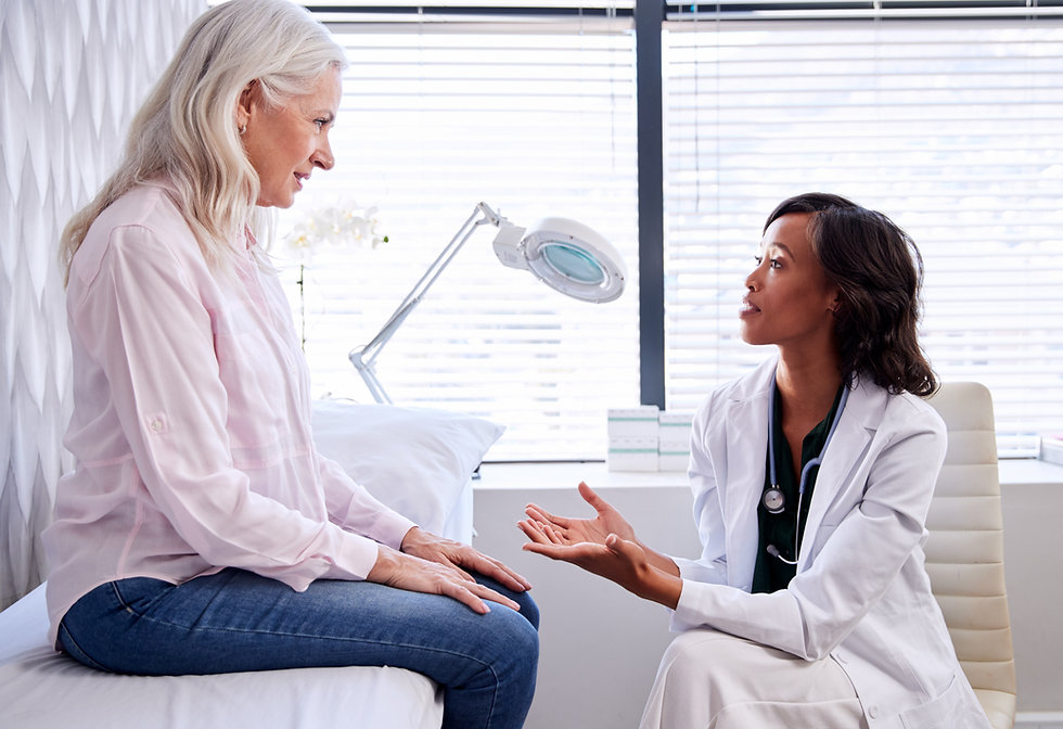Mature Woman In Consultation With Female Doctor Sitting On Examination Couch In Office_edited.jpg