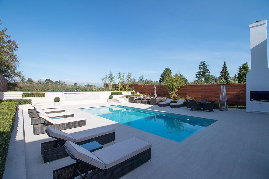 Blue sky above a contemporary garden with white porcelain paving and large swimming pool