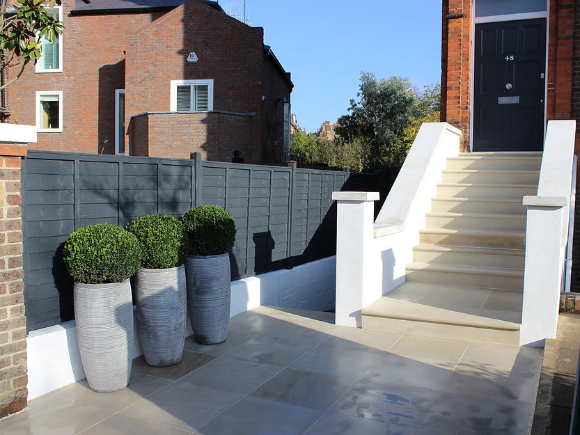 Paved garden steps leading to a black house door, with blue sky and a painted dark grey fence