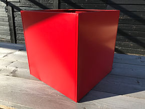 Bright red painted metal cube planter on a sunny day in front of a black wooden building. Made by Metal Planters UK.jpg