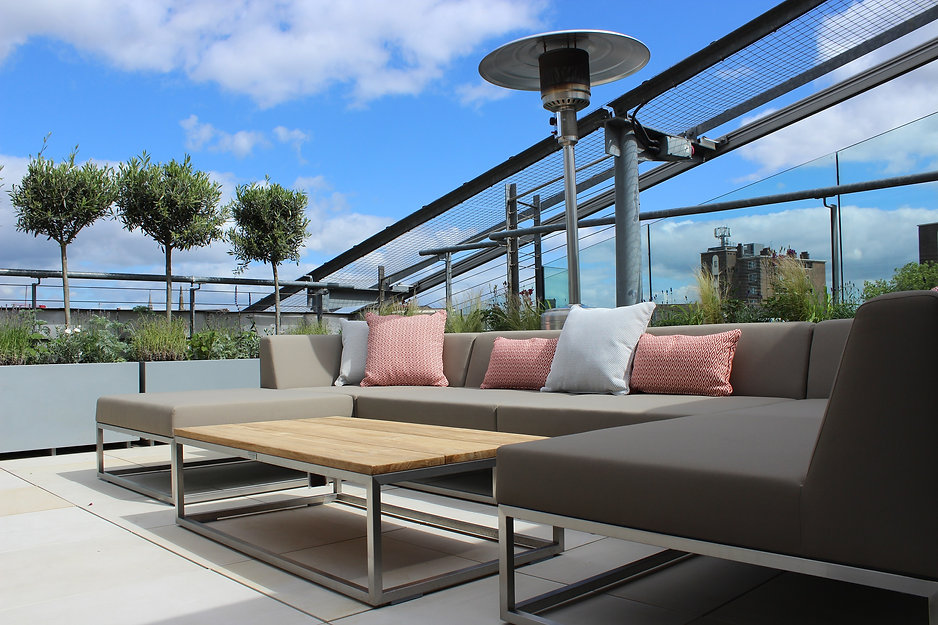 Large metal garden sofa on a roof terrace on a sunny day with blue sky