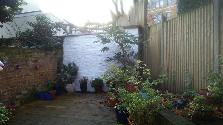 Decked garden with a white brick wall an plants in pots