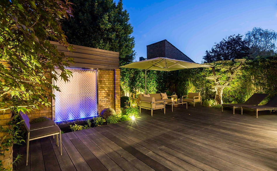 Night-time decked rear garden with lighting and a stainless steel fish scale water wall