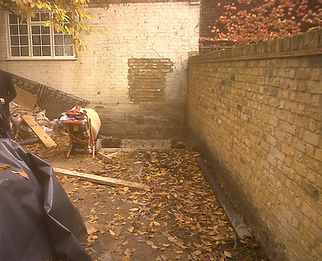 Small garden before landscaping works are carried out. Brick walls and cement mixer