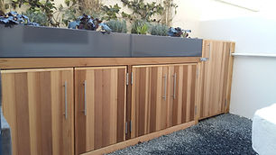 Outdoor cedar cupboard with powder coated metal planters in a front garden