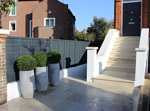 Paved front garden with steps leading to house, with white rendered walls and grey painted fence