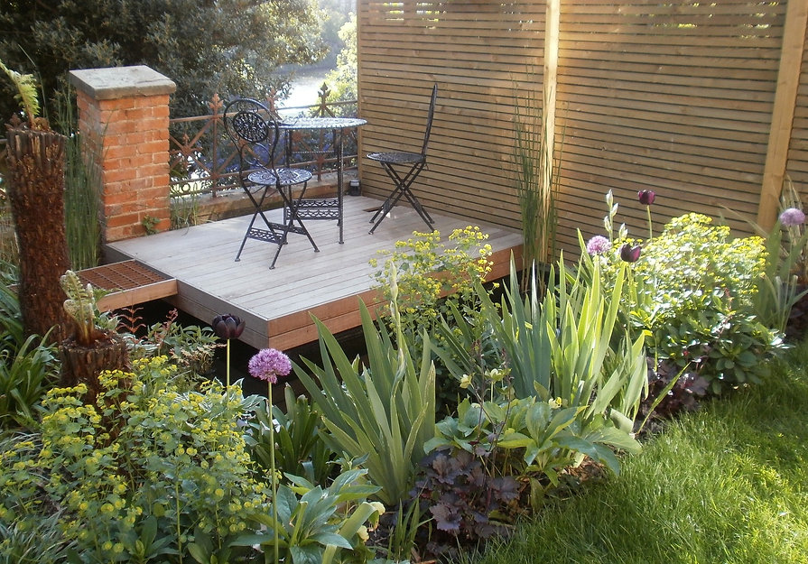 Garden with a deck floating over a pond, with a slatted timber fence and distant views of the river thames