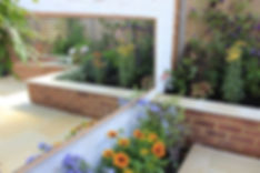 A-smart-small-garden-reflected-in-a-wall-hung-garden-mirror-above-orange-and-purple-flowers