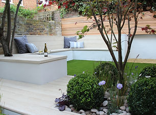 Chic garden with built-in corner seating, artificial beige decking and artificial grass.