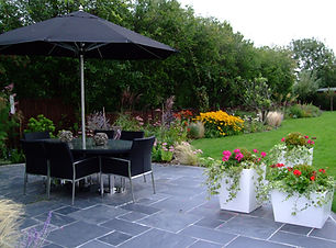 Large garden in the countryside with a big slate patio, garden dinning table and huge lawn