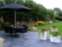 Black outdoor dining table and chairs on a grey slate patio
