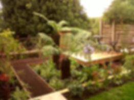Metal grid walkway between tree ferns in a tropical style garden