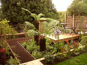 Tropical garden with large tree ferns next to a metal grid walkway, leading to a hardwood deck floating over a pond.