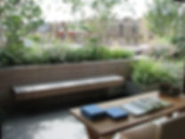View from a desk onto a roof garden with naturalistic plating and a floating wooden bench
