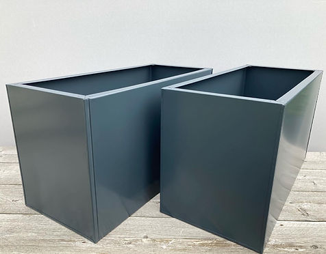 A pair of anthracite grey powder-coated metal planters, in RAL 7016, on a wooden table with light grey background, by Metal Planters UK