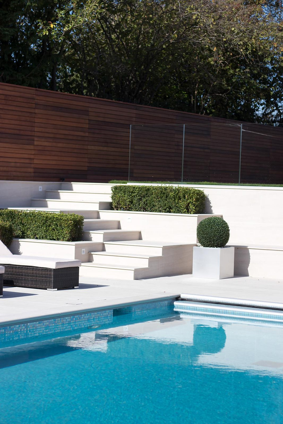 Flight of porcelain tiled steps leading from a swimming pool to a lawn