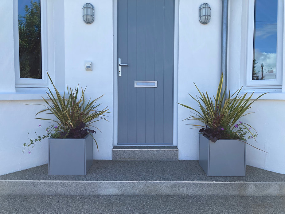 Pair of matching powder-coated metal planters either side of a house dorway, planted with phormiums and heuchera