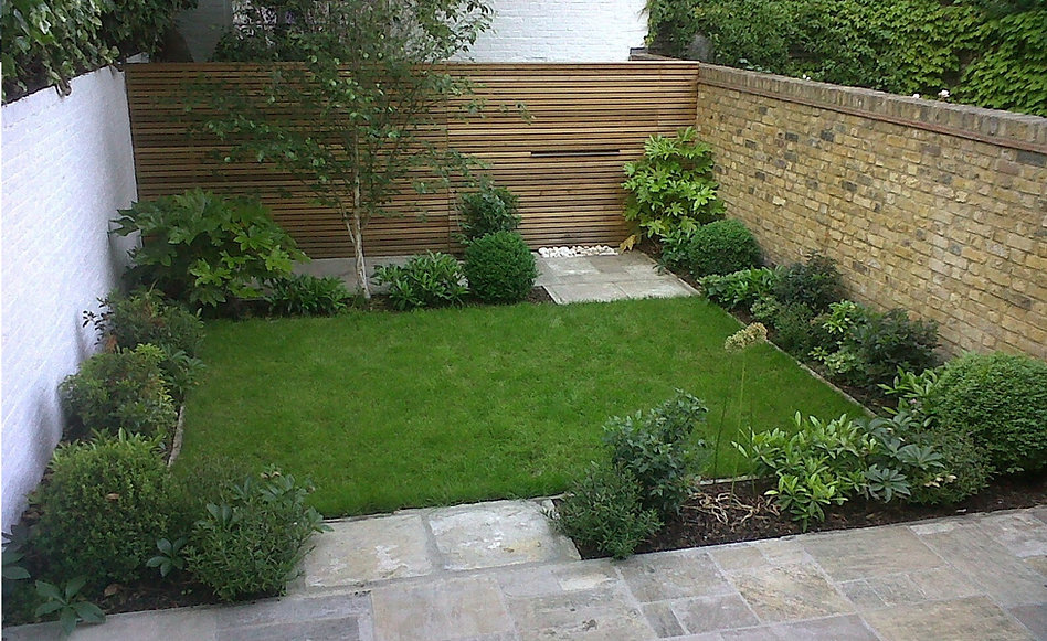 Small lawned garden with evergreen planting, york stone patio and cedar fence