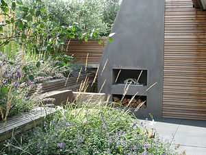 Outdoor concrete fireplace in garden, with nauralistic planting and wooden screening