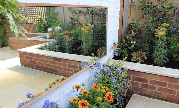 Paved garden with large wall mounted mirror and colourful flowers
