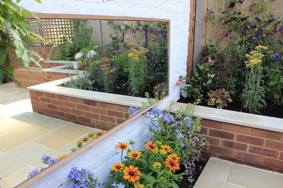 small garden with large mirror fixed to a white brick wall