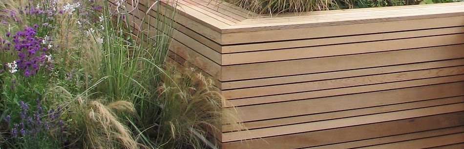 Multi-width bands of cedar forming a screen around naturalistic planting