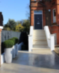 Beige paved garden steps with white rendered walls and dark grey painted fence, against a bright blue sky on a sunny day
