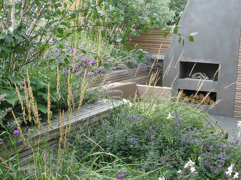 Concrete outdoo fireplace surrounded by wild planting and cedar screening