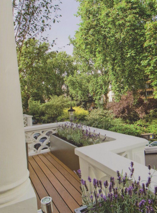 Powder coated metal planter plante with lavender on a decked balcony