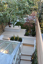 Small garden with beige artificial decking steps, cedar screening and artificial grass at the rear.