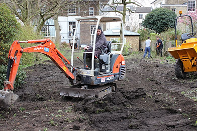 Man on a Kubota digger in a garden