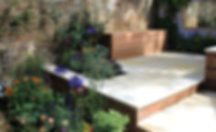 Beige-sawn-sandstone-paving-in-a-small-garden-with-yellow-brick-walls-and-perennial-plants