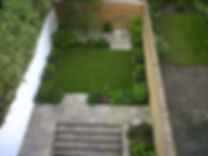 Overhead view of a nice small town garden with a small square lawn, york stone patio and evergreen plants