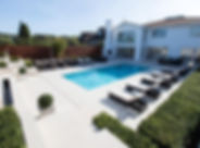 White paving surrounding a blue outdoor swimming pool in a sunny high-end garden