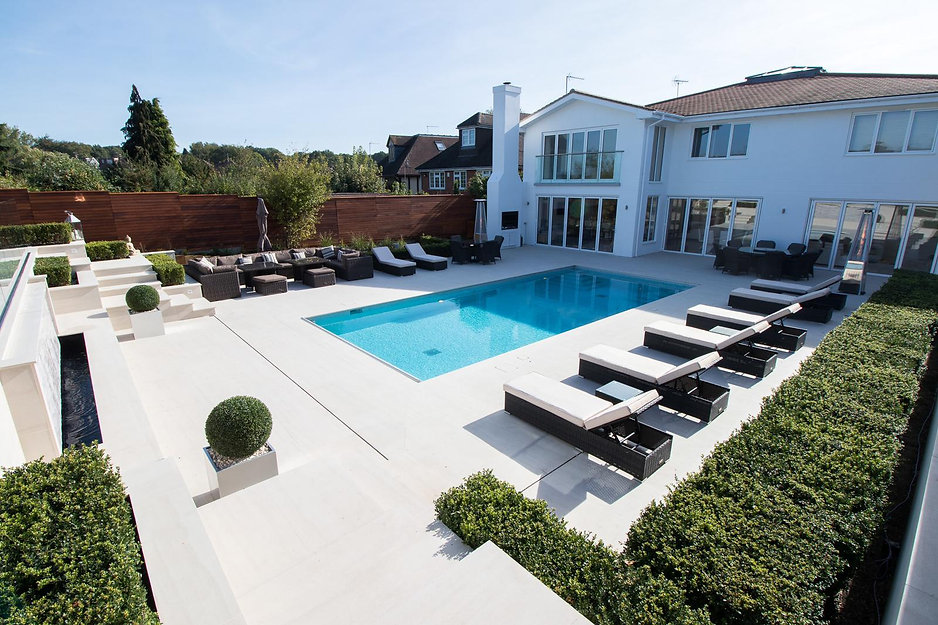 Large garden with bright blue swimming pool in the centre, surrounded by loungers and contemporary house