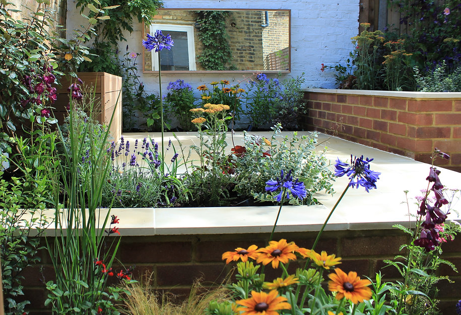 paved-small-city-garden-with-colourful-plants-and-a-wall-mounted-garden-mirror
