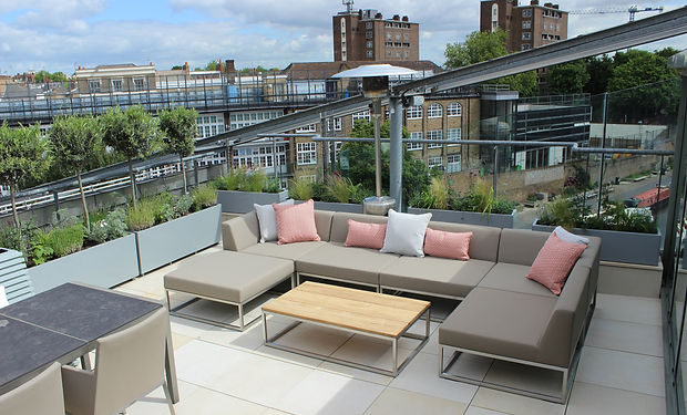 Roof terrace with outdoor sofa and metal planters overlooking canal