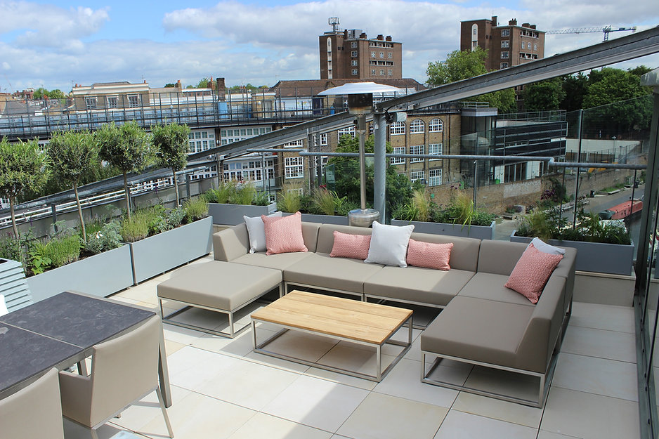 Outdoor sofa on a paved urban roof terrace overlooking canal.