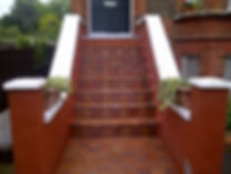 Bright red tiled garden steps leading up to a front door