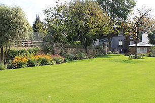 A huge, perfectly flat lawn, bordered by a long colourful flowerbed.