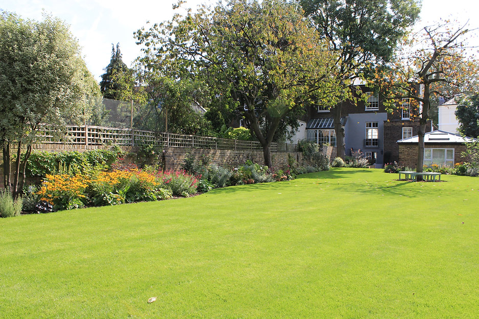 Large lawned garden with a long planting bed running along side a reclaimed brick wall