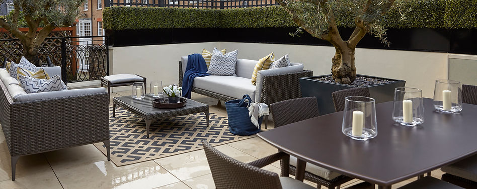 Garden sofa set and outdoor rug on limestone paving, surrounded by white rendered walls and artificial hedges