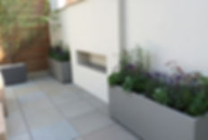 Garden on a city roof terrace with a outdoor fireplace built into a white rendered wall, with grey metal planters planters on either side.