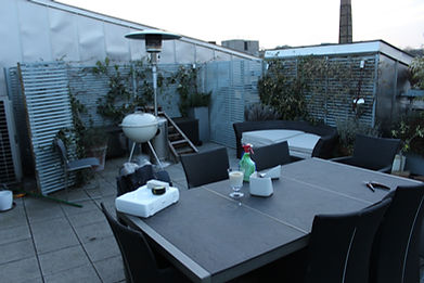 A roof terrace in need of renovation, with a large dning table in the forground