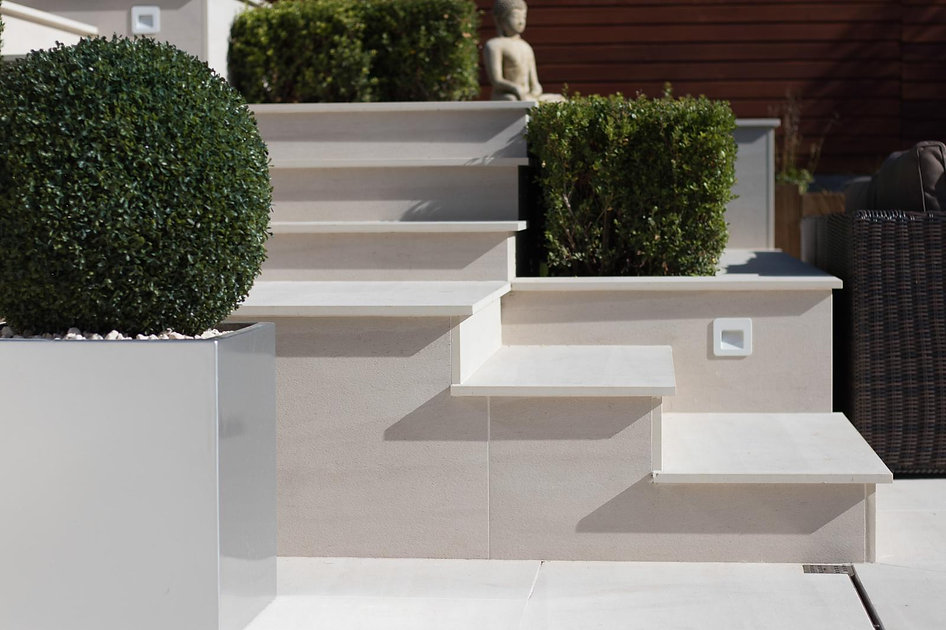 Close up of porcelain tiled grden steps, with clipped hedges and metal planter.
